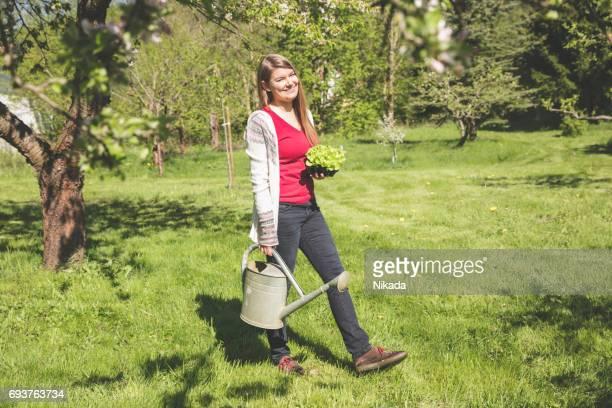 Porträt einer Frau zu Fuß mit Gießkanne im Garten