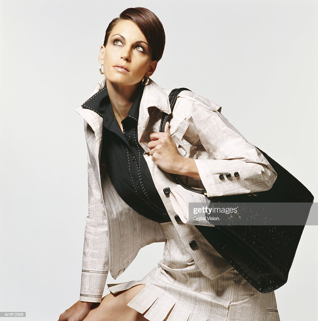 Portrait of a Woman Wearing a Jacket made from Paper Carrying a Handbag : Stock Photo