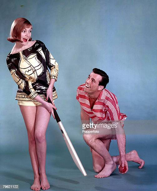 1958 A portrait of a woman wearing an artistic shirt and shorts holding a cricket bat ready to hit a ball which a man with her is holding and about...