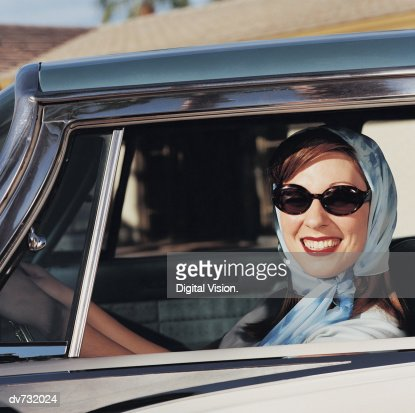 Portrait of a Woman Wearing Sunglasses and Headscarf in Her Car : Stock-Foto