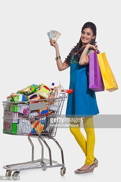 Portrait of a woman with a shopping cart , shopping bags and currency