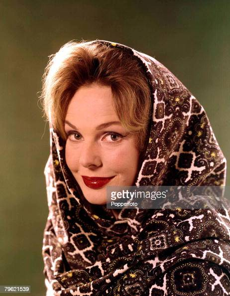 1960 A portrait of a woman with blonde hair smiling at the camera with a patterned blanket wrapped around her head and shoulders