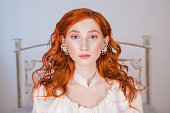 Portrait of a woman with long red curly hair in a white vintage wedding dress with white pearl earrings on her ears. Red-haired girl with a pale skin, blue eyes, a bright unusual appearance in bedroom