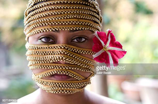 Portrait of a woman wrapped with golden beads.