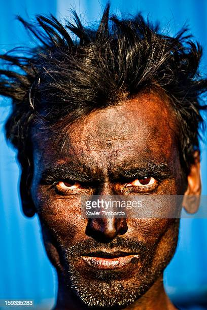 Portrait of a worker with his face covered by soot of coal preparing a boiler for processing and colourdyeing fabric in Rajasthan on January 13 2012