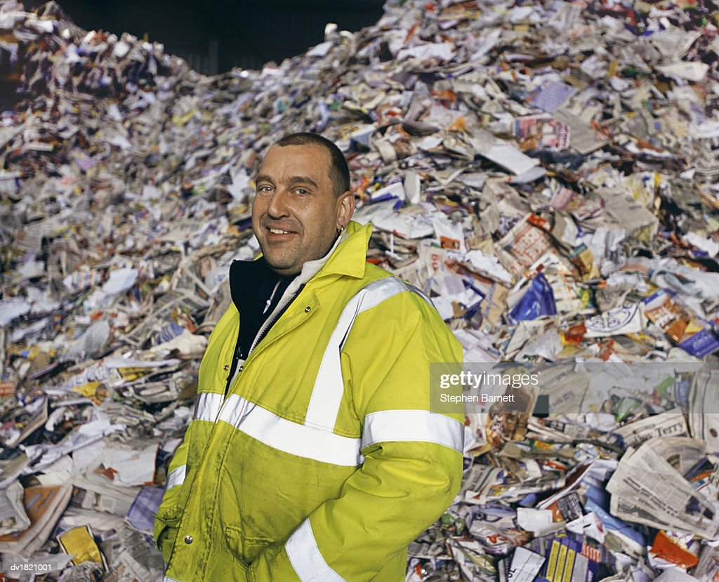 Portrait of a Workman in a Fluorescent Jacket Standing in Front of a Pile of Paper for Recycling : Stock Photo