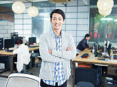 confident young asian entrepreneur standing in own company looking at camera arms crossed smiling.