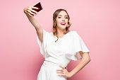 Portrait of a young attractive woman making selfie photo with smartphone on a pink studio background