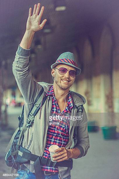 Portrait of a young Backpacker waving on the train station