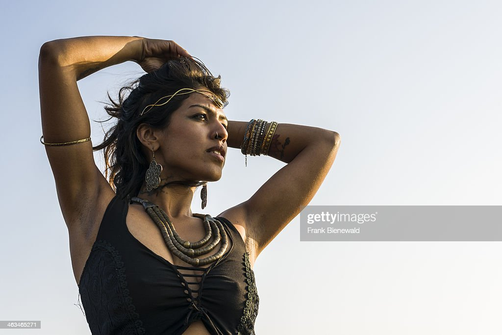 Portrait of a young, beautiful Indian women wearing fashionable clothes and jewellery on the beach.