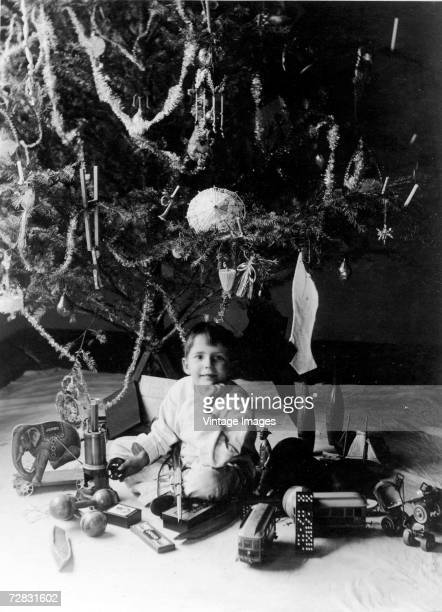 Portrait of a young boy as he sits in his pyjamas underneath a Christmas tree among his presents early twentieth century Among the presents are a...