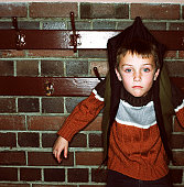 Portrait of a young boy (8-10) attached to a coat hook by his jacket