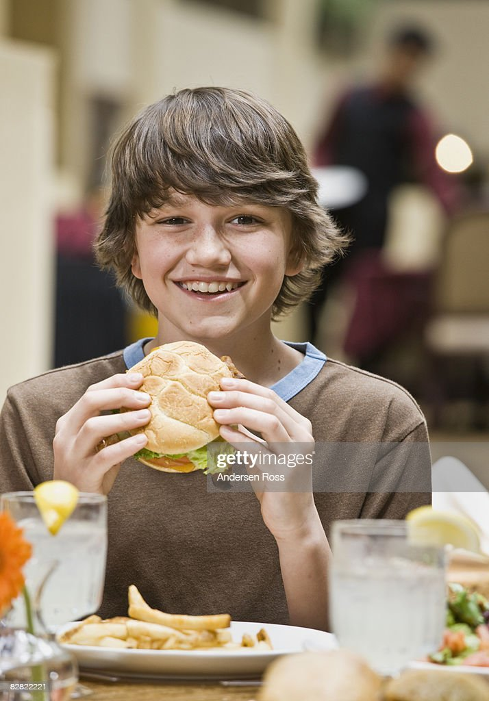 Portrait of a young boy eating a hamburger : Stock Photo