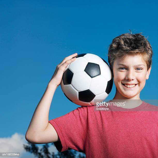 portrait of a young boy holding a football on his shoulder