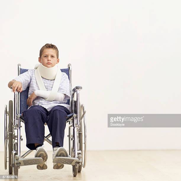 Portrait of a young boy (8-10) in a wheelchair wearing a neck brace