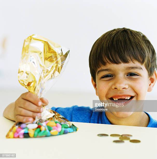 Portrait of a young boy (6-8) laughing holding a bag of candy and money coins on counter in front of him