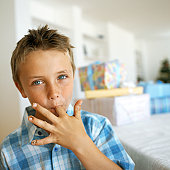 portrait of a young boy licking his finger