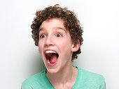 Close up portrait of a boy with mouth open having a surprised expression