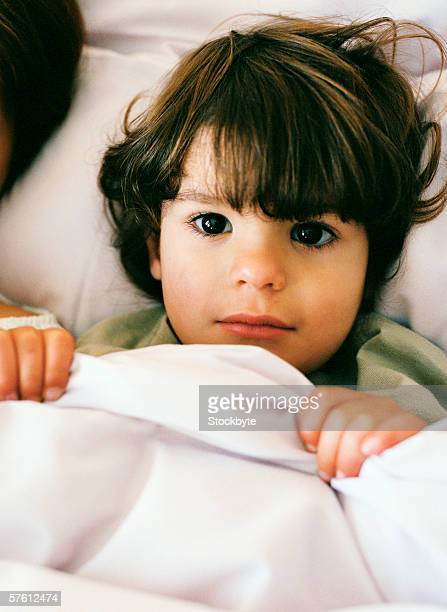 Portrait of a young boy (4-6) lying in bed holding a cover