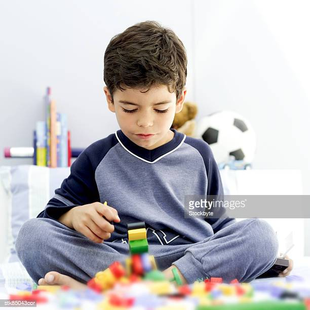 portrait of a young boy playing with building blocks