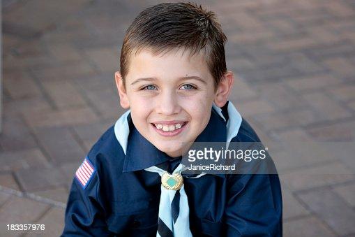 Portrait of a young boy scout in blue uniform smiling