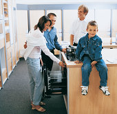 Portrait of a Young Boy Sitting on An Oven in a Department Store Whilst His Parents Talk to a Shop Assistant