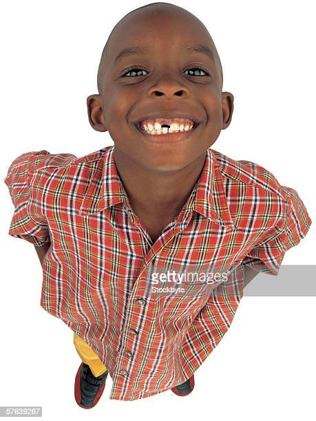 Portrait of a young boy (6-8) smiling with a tooth missing