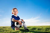 Young hispanic soccer player smiling with ball