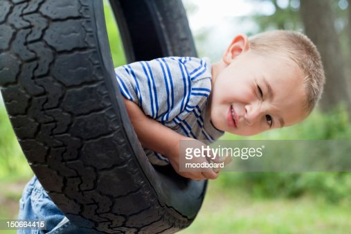 Portrait of a young boy winking while swinging on tire : Foto de stock