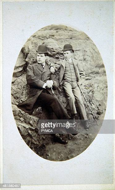 Portrait of a young boy with a man sat on rocks circa 1910s