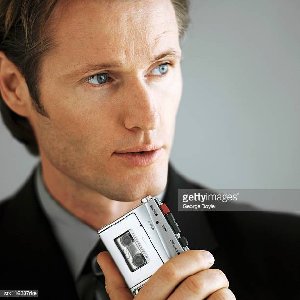 portrait of a young businessman making notes on a cassette recorder