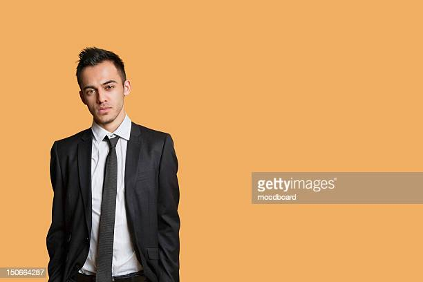 Portrait of a young businessman over colored background