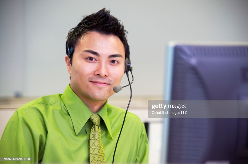 Portrait of a young businessman wearing a headset sitting in front of a computer screen : Stock Photo