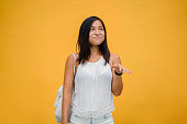 She is dressed in comfortable and casual blouse and denim shorts. She is petite, tanned, athletic, and cute. She is smiling playfully as she poses for her portrait.