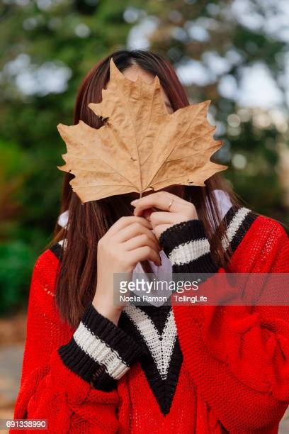 Portrait of a young Chinese woman covering her face with an autumn leaf