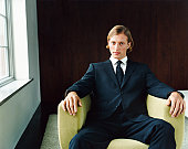 Portrait of a Young, Confident Man in a Black Suit Sitting in an Armchair by a Window
