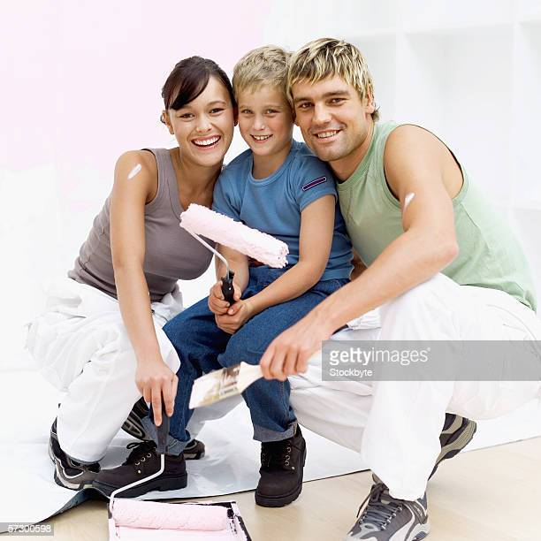 Portrait of a young couple and a young boy (8-10) holding painting equipment