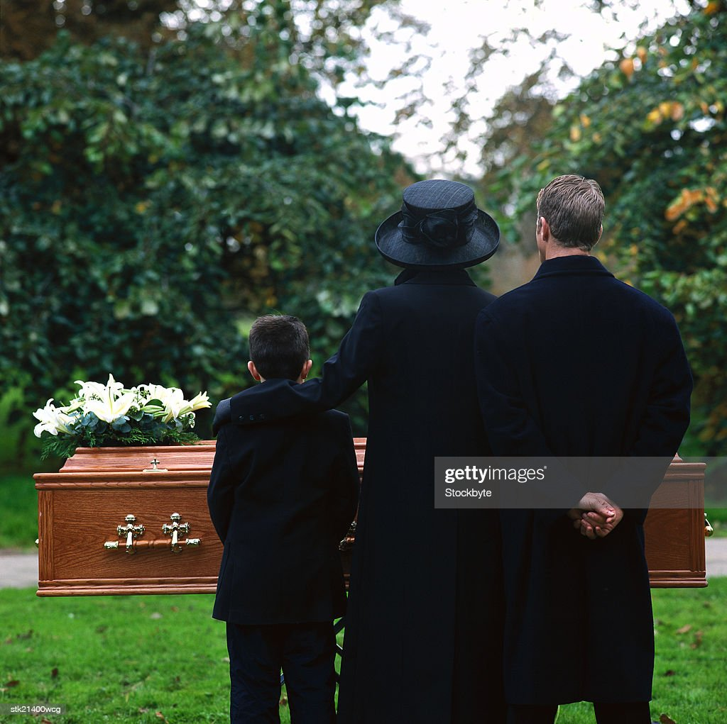 portrait of a young couple and their son standing in a cemetery : Stock Photo