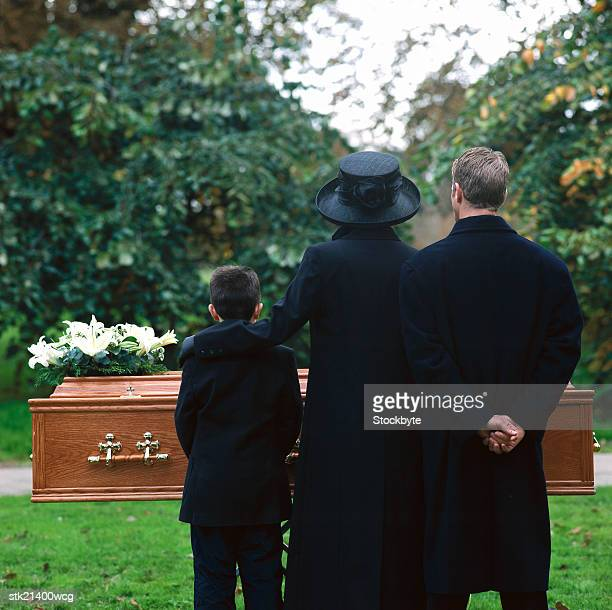 portrait of a young couple and their son standing in a cemetery