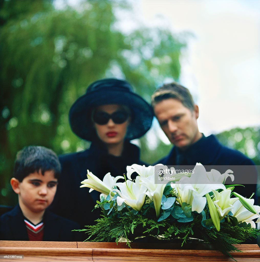 portrait of a young couple and their son standing over a coffin : Stock Photo