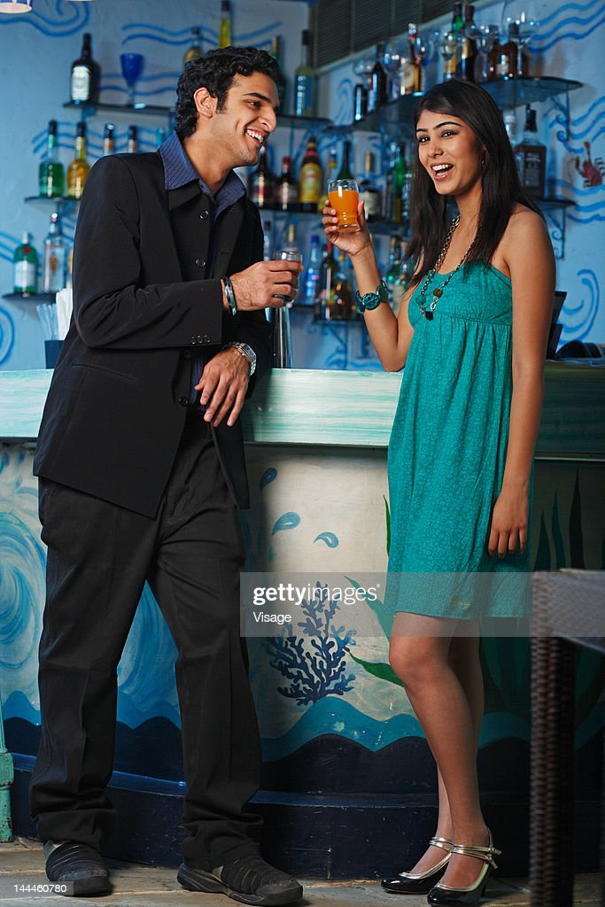 Portrait of a young couple at a bar enjoying : Stock Photo