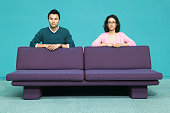 Portrait of a young couple behind a couch