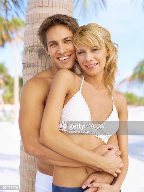 Portrait of a young couple leaning against a palm tree and hugging