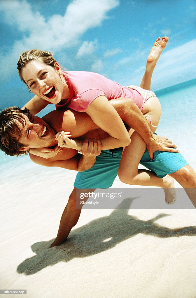 portrait of a young couple playing at the beach : Stock Photo