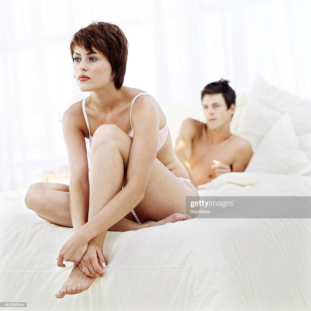 portrait of a young couple sitting apart on a bed : Stock Photo