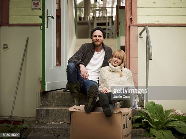Portrait of a young couple sitting infront of their new house