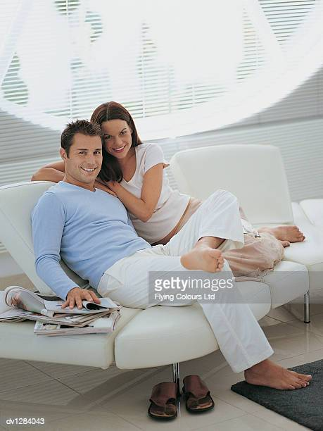 Portrait of a Young Couple Sitting on a Sofa in Their Sitting Room