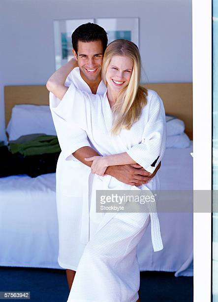 portrait of a young couple standing in bathrobes holding each other