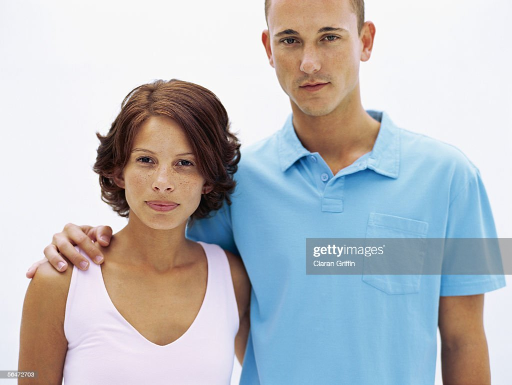 portrait of a young couple standing together with their arms around : Stock Photo