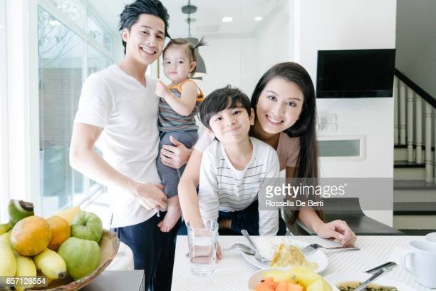 Portrait of a young family having breakfast in the kitchen
